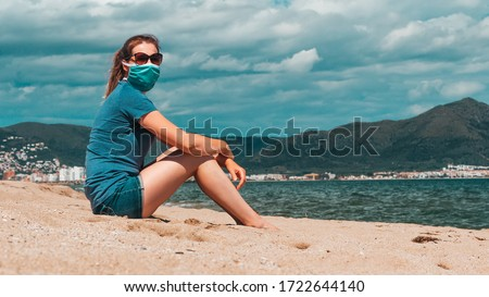 Young woman in sunglasses and medical mask sitting alone at the beach, new normal concept. Life after coronavirus pandemic, travel and vacations at sea with new rules theme