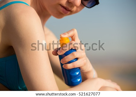Young woman in sunglasses holding bottle of sunscreen lotion, spraying sunblock cream on shoulder before tanning, close up. Sunburn and cancer prevention concept #521627077