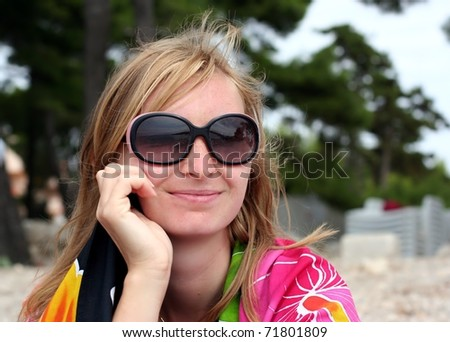 Young woman in sunglasses is smiling and muse upon a distant scene