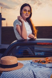 Young woman in sunglasses, white t-shirt is posing in yellow car roadster with pizza, striped cloth and hat on its trunk. Fast food. Close up