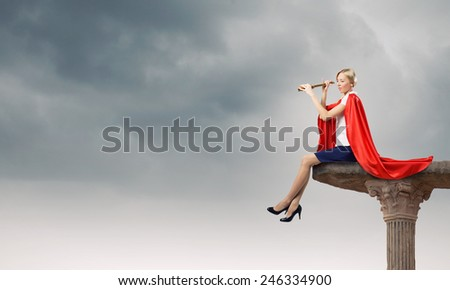 Young woman in super hero costume looking in spyglass #246334900