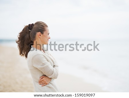Young woman in sweater on beach looking into distance - Shutterstock ID 159019097