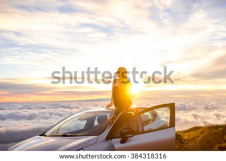 Photo of Young woman in sweater with heart shape enjoying beautiful cloudscape sitting on the car roof above the clouds on the sunrise. Wide angle image with a lot of space