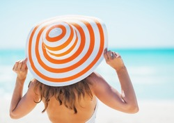 Young woman in swimsuit beach hat looking into distance . rear view