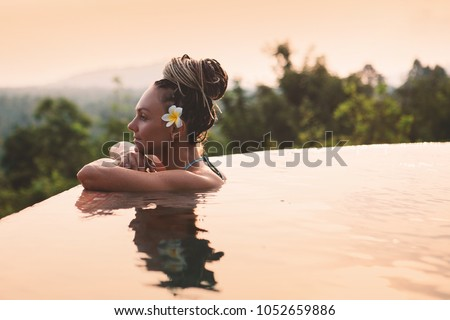 Young woman in swimsuit relaxing next to the infinity pool with jungle view during vacation retreat #1052659886