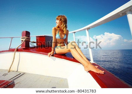 Young woman in swimsuit sitting on yacht at sunny day and looking to somewhere