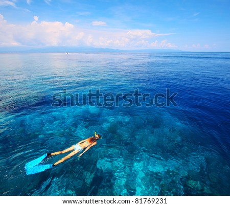 Young woman in swimsuit snorkeling in blue and transparent tropical sea