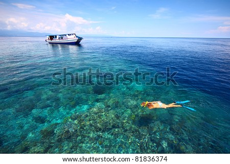 Young woman in swimsuit snorkeling in blue and transparent tropical sea not far away from a boat