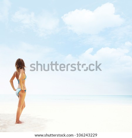 Young woman in swimsuit standing on a white sand and looking to a blue clear sky