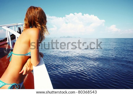Young woman in swimsuit standing on yacht at sunny day and looking to a sea