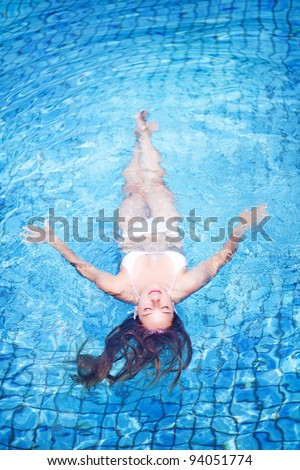 Young woman in swimsuit, swimming in pool, top view