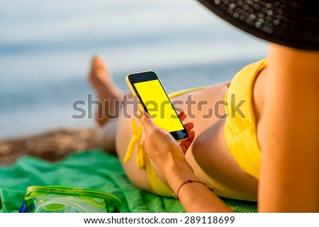 Young woman in swimsuit using mobile phone with empty screen for copy paste lying on the green towel on the beach. Focused on the hand with phone.