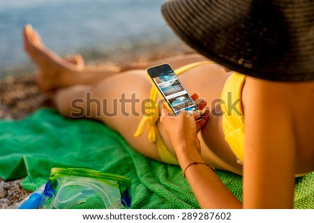 Young woman in swimsuit watching website with beach photos on mobile phone lying on the green towel on the beach. Focused on the hand with phone.