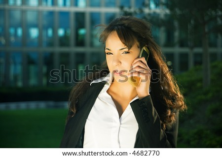 Young woman in the evening sun using her cellphone in front of a modern glass and steel building
