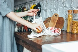 Young woman in the grey dress pulls apples out of knitted rag bag string bag shopper in the kitchen, zero waste, slow life