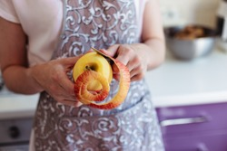 Young woman in the kitchen peels and slices an apple