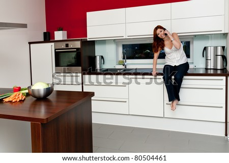 Young woman in the kitchen talking on the phone