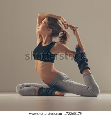 Young woman in the Pigeon yoga pose.