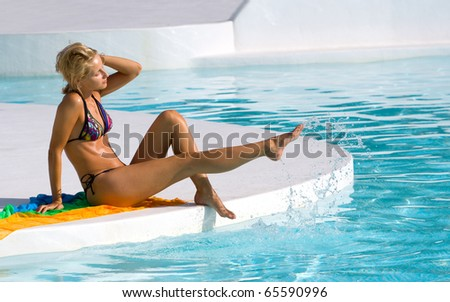 Young woman in the pool playing with water