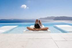 young woman in the swimming pool ,infinity pool relaxing looking out over the ocean caldera of Oia Santorini Greece