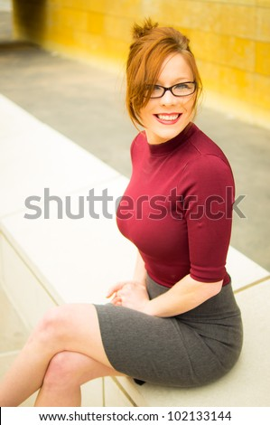 Young Woman In Tight Business Attire Sitting in Plaza - stock photo