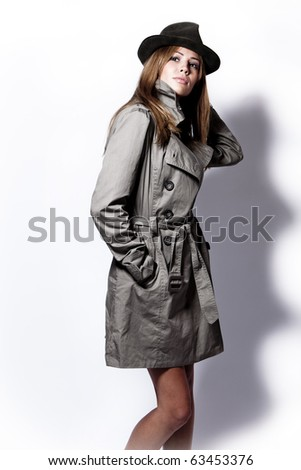 young woman in topcoat and  black hat, studio shot