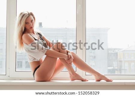 young woman in underwear sitting on windowsill