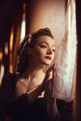 young woman in vintage clothes looking out the window inside a retro train