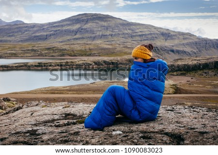 Young woman in warm blue sleeping bag ,  on the stones with northern mass, Iceland #1090083023