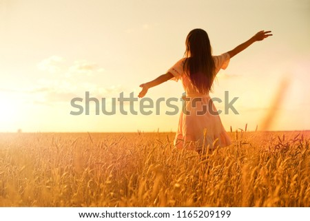Young woman in wheat field at sunset