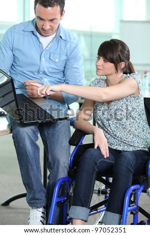 Young woman in wheelchair being shown something on a laptop computer