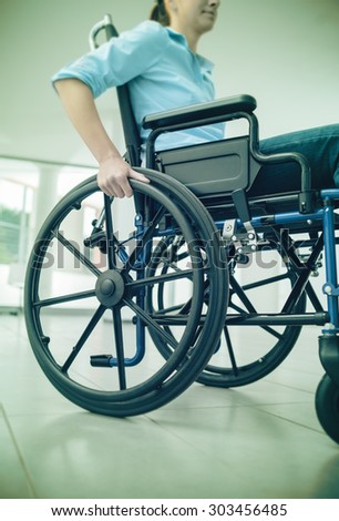 Young woman in wheelchair hand pushing on wheel close up, disability and handicap concept