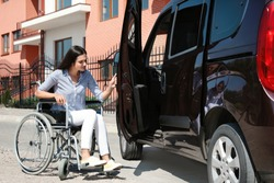 Young woman in wheelchair opening door of her van outdoors