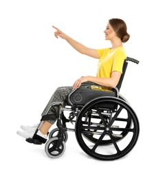Young woman in wheelchair pointing on something isolated on white