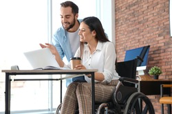 Young woman in wheelchair with colleague at workplace