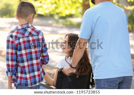 Young woman in wheelchair with her family walking outdoors #1195723855