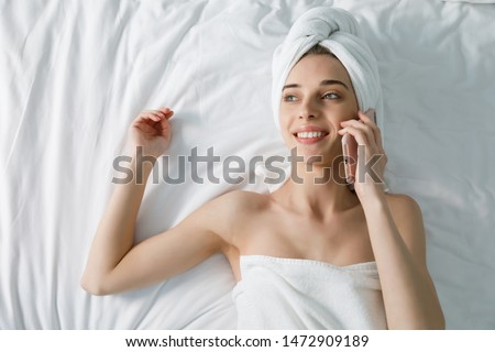 Young woman in white bath towel chatting on mobile phone in bed at home #1472909189