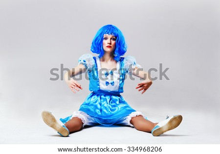 Young woman in white-blue dress with blue hair sitting like a doll     Stock photo ©