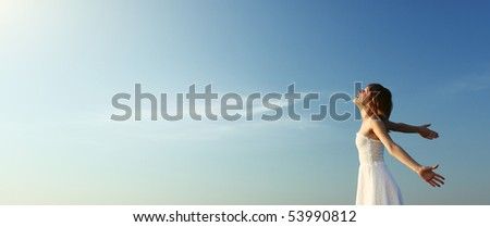 Young woman in white dress over blue sky background enjoying the sun - stock photo