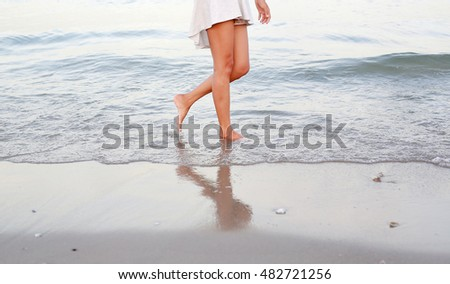 Young woman in white dress walking alone on the beach #482721256