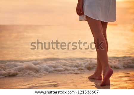 Stock Photo Young woman in white dress walking alone on the beach in the sunset