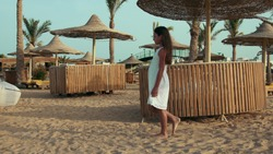 Young woman in white dress walking at sand beach with cane umbrellas and sunbeds. Long hair girl enjoying summer holiday at egyptian seaside. Slim lady looking at pictorial view at seashore.