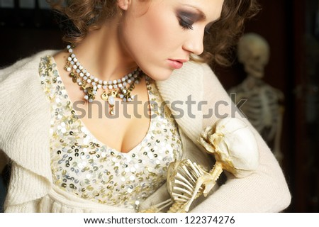 young woman in white dress with cranium in the hand