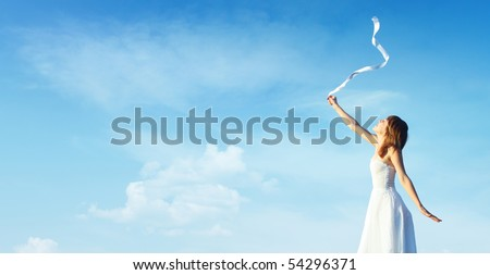Young woman in white dress with white ribbon over blue cloudy sky background