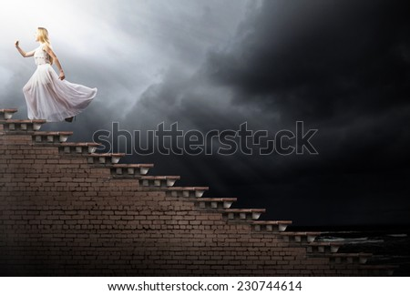 Young woman in white long dress stepping up the staircase #230744614