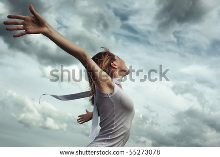 stock photo : Young woman in white shirt with raised hands over stormy cloudscape