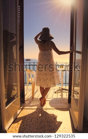 Young woman in white summer dress gazing at mediterranean sea, standing on a hotel balcony at sunset.