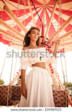 young woman in white summer dress in amusement park stand by carousel