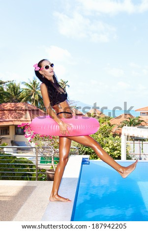 Young woman in white sunglasses with pink inner tube having fun at tropical resort in summer day. Outdoors