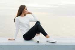 Young woman in white sweater and black leggings is resting after jog on promenade. Lifestyle, beauty, walking outdoors